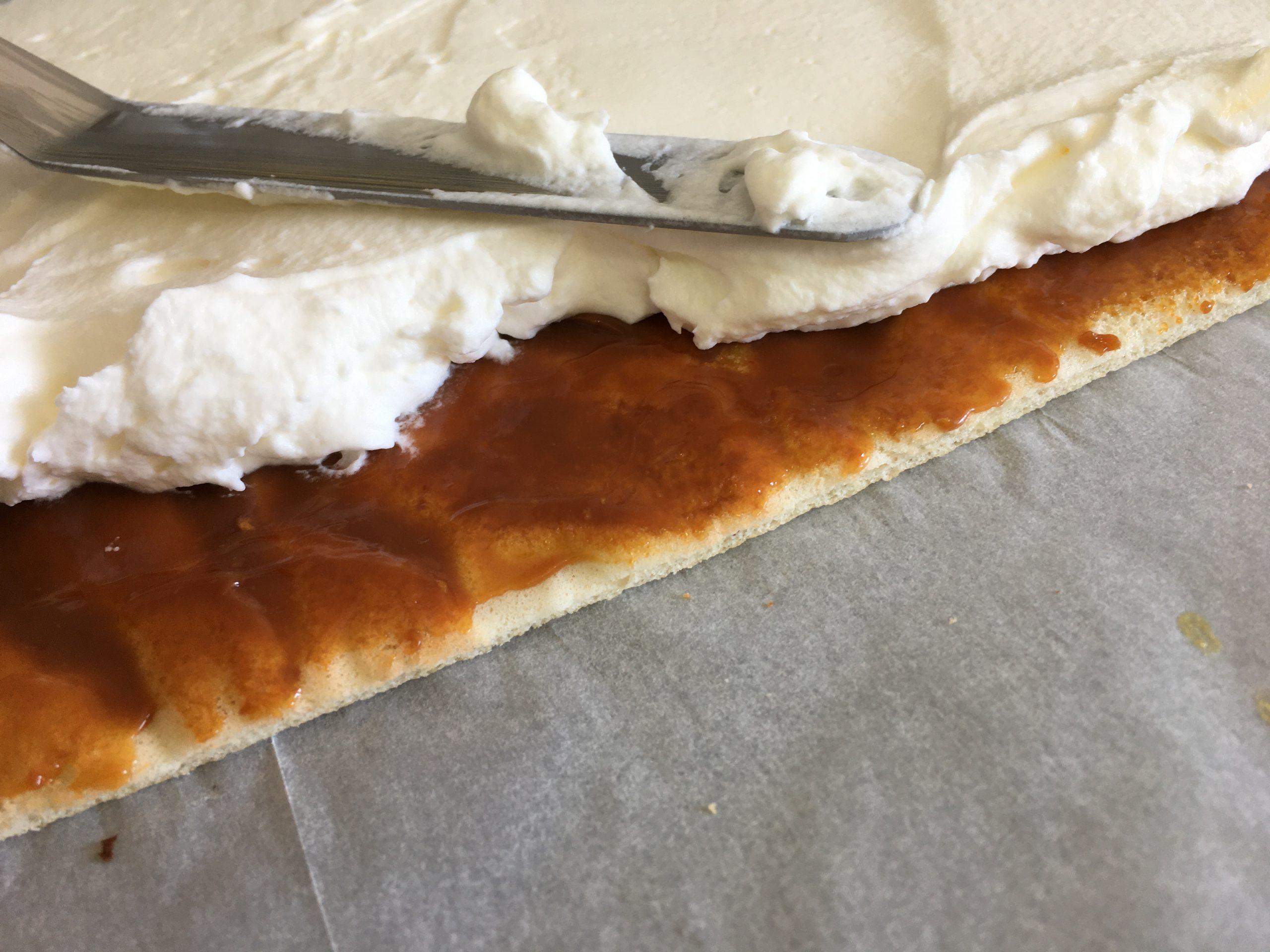 מורחים את ריבת החלב על הרולדה בעזרת פלטה קטנה, לאחר מכן מורחים את הקרם ומיישרים.
